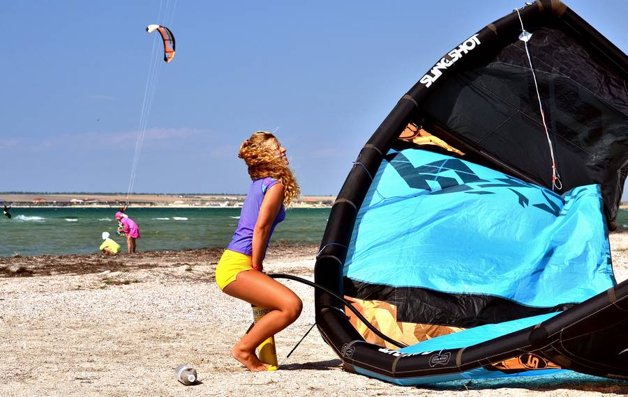 girl pumps up kite on the beach